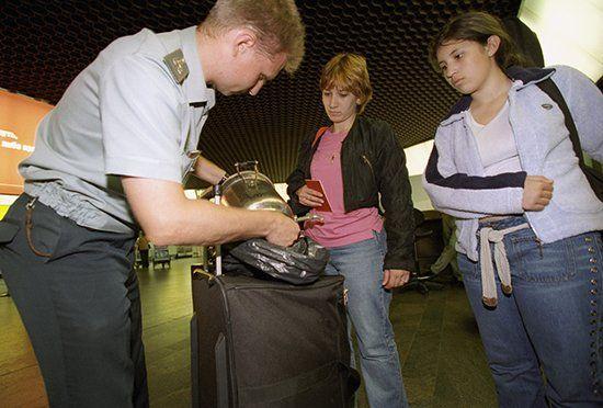 Таможенник осматривает багаж