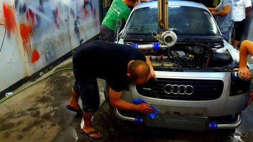 Мужчина моет машину после ремонта